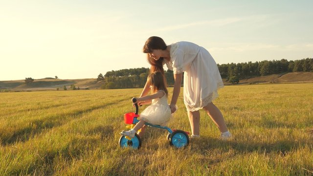 Mom teaches daughter to ride a bike. Mother plays with her little daughter. small child learns to ride a bike. concept of happy childhood.
