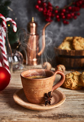 Hot coffee in clay cup with star anise on old wooden board with homemade cookies. Christmas composition with festive decor.