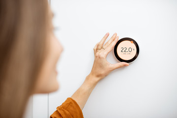 Young woman regulating heating temperature with a modern wireless thermostat installed on the white wall at home. Smart home heating regulation concept