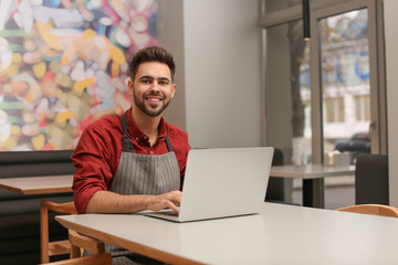 Young male business owner working with laptop in his cafe Fotoväggar