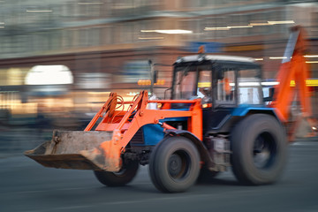 Blurred motion of excavator-loader speeding on city street. Tractor moving fast on the road. Municipal vehicle. Tractor, excavating and loading equipment. Defocused image, Blur background