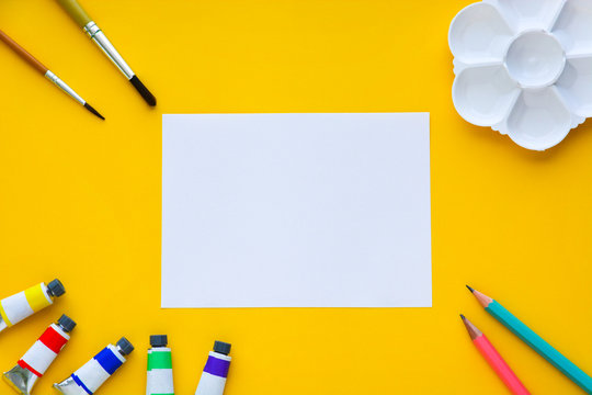 top view of brushes, color tubes, pencils, palette and white paper on yellow background, copy space, flat lay, paintings art concept