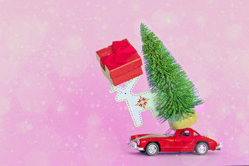Krasnodar, Russia - December 10, 2019: Red  car with a christmas tree on the roof, toy and gift box, blue background. Copy space . Concept new year.