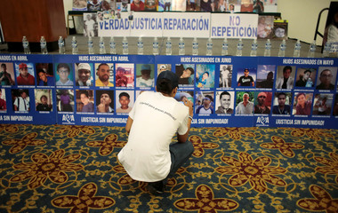 A demonstrator uses his cellphone to take photos of images of protesters who died during the protests against Nicaraguan President Daniel Ortega's government in 2018, in the commemoration of International Human Rights Day in Managua