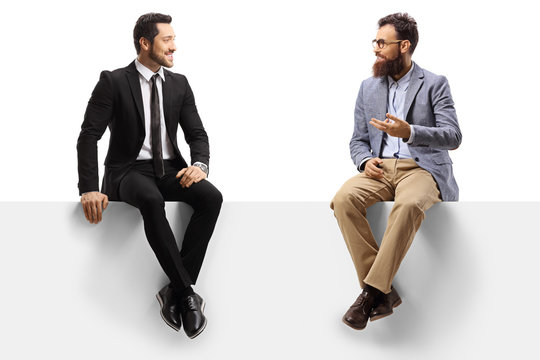 Man in a suit and a bearded man sitting on a blank panel and talking