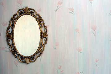 Old antique gold mirror hanging in a vintage room with old pattern wallpaper