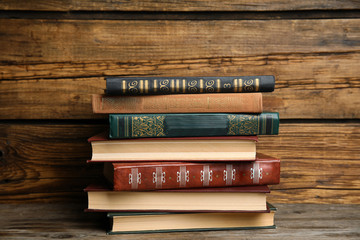 Collection of different books on table against wooden background
