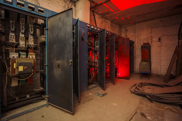 Switchgear cabinets with broken hardware in abandoned factory