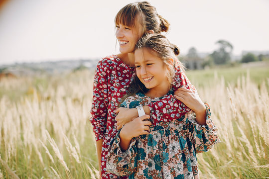 Fashionable mother with daughter. Family in a summer fiels. Girl in a red dress.
