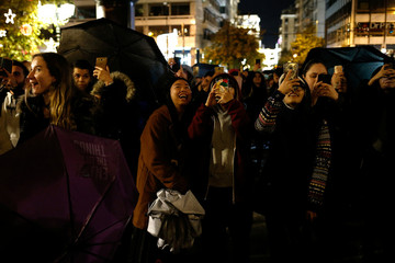 People take pictures during a Christmas tree lighting ceremony on Syntagma square in Athens