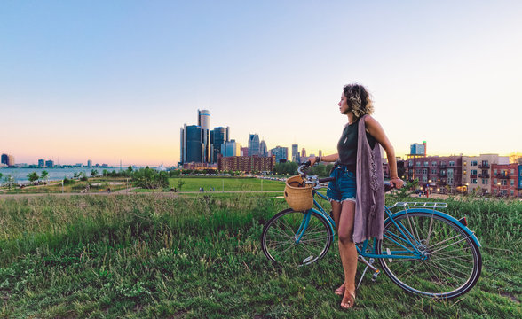 Young woman with bicycle with Detroit Skyline during sunset