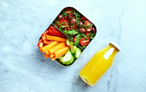 Raw vegetables and tomato salad with olives and arugula in a lunch box. Fresh orange juice in a bottle.Take out food