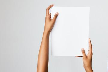 Fototapeta Woman of color holding a letter size or A4 brochure mockup obraz