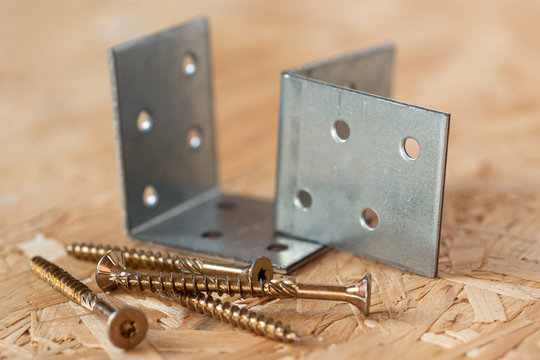 Two galvanized angle brackets and self drilling screws lying on chip board. Blurred background.