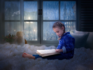 Little girl with a book late at night in a cozy children's room on the bed