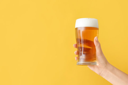 Hand with glass of beer on color background