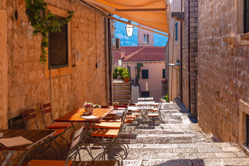 Medieval street with stairs and cafe tables in famous european city of Dubrovnik on a sunny day.