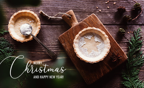 Traditional homemade Christmas pie on dark wooden background / Merry Christmas greeting text