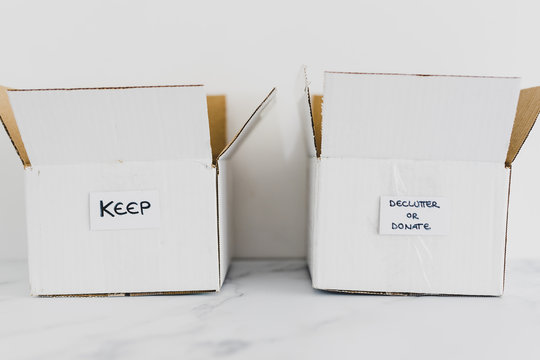 decluttering concept, storage boxes to sort between objects to keep and those to declutter or donate with labels