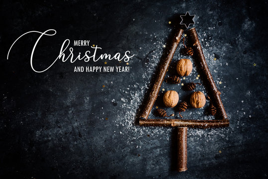 Christmas themed greeting card with christmas tree shaped branches on a rustic, dark background and greeting text