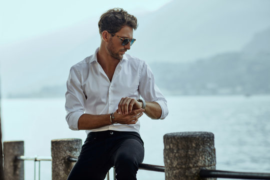 Stylish man in white shirt checking the time over the mountains background