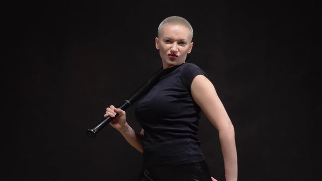 beautiful short haired blond woman  with a baseball bat on black background