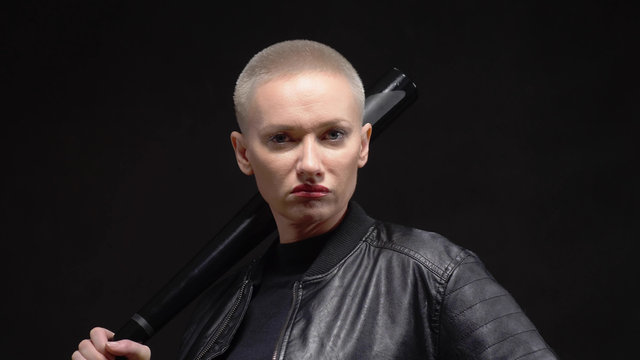 short haired blond woman in a black leather jacket with a baseball bat