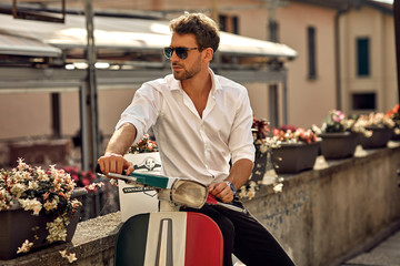 Stylish italian man wearing white shirt and sitting on classic scooter Fotomurales