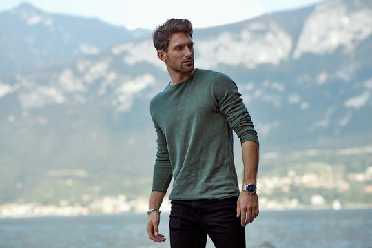 Handsome man in casual style clothes over blured mountain background