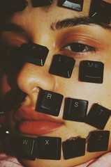 Close up of keyboard keys on woman's face