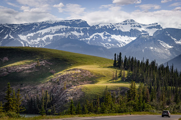 A lone vehicle is dwarfed by magestic Rocky mountains in Jasper National Park, Alberta, Canada