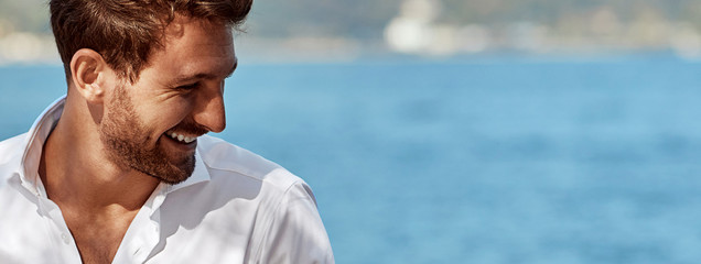 Portrait of smiling handsome man in elegant white shirt standing near the lake in the alps Papier Peint