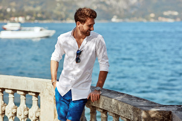 Portrait of smiling handsome man in elegant white shirt standing near the lake in the alps