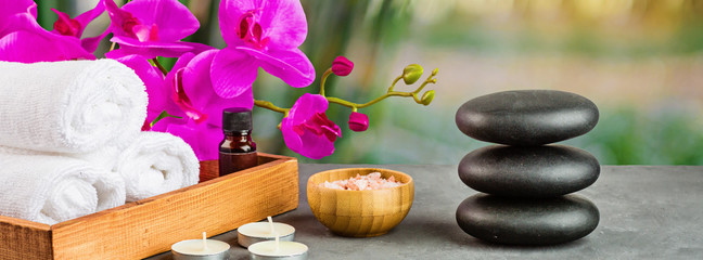 Stores photo Spa hot spa stones set for massage treatment, orchid flower, towels, candles and sea salt on green background with bamboo. Elegant and luxury spa. mock up, template. Health and beauty care concept