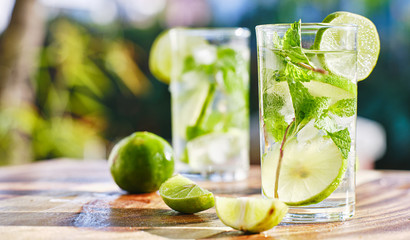 two mojito cocktails on wooden table top