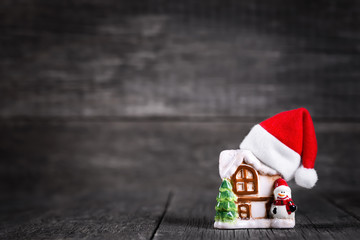 Santa Claus hat on toy of house with spruce tree and snowman over wooden rustic background.