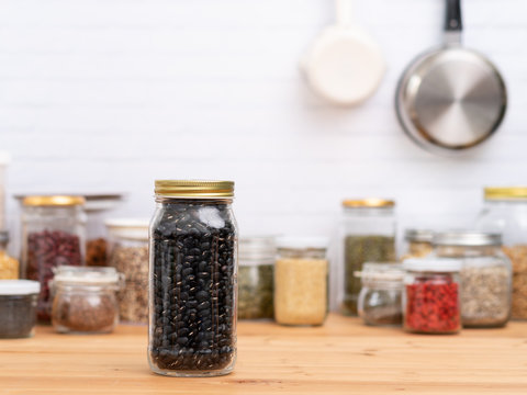 Beautiful glass jar container full of dried black beans on the wooden kitchen counter with other dry ingredients - beans, peas, grains all the nutrients source for Plant-based diet and Vegan