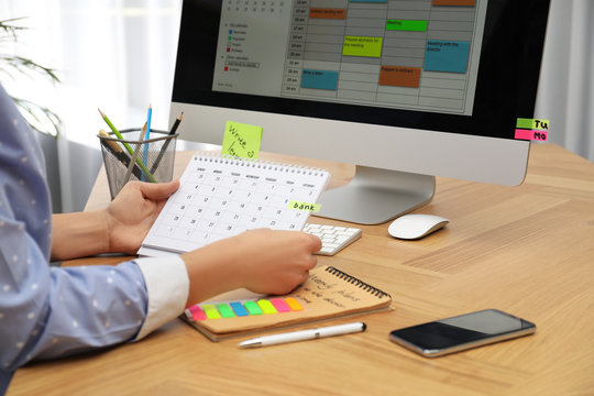 Woman making schedule using calendar at table in office, closeup