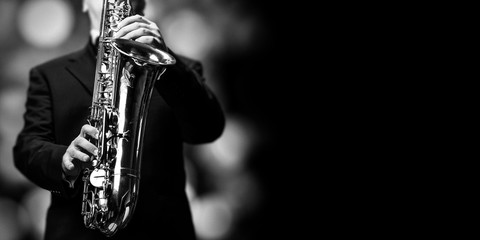 The saxophone player at the jazzclub - open place for text on black background