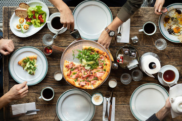 Friends at the table eat pizza. The company gathered in a restaurant. Lunch, a snack at work. Pizza party. People take slices of pizza. Table setting. People eat fast food. Coffee on the table.