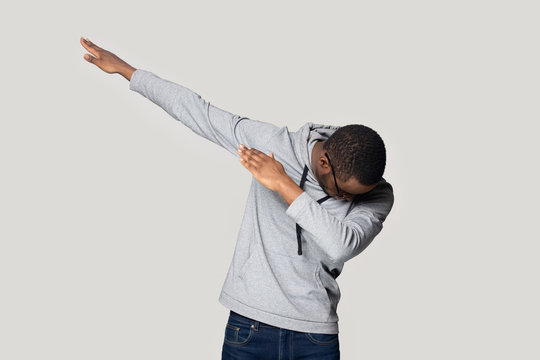 Happy young african american guy in sportswear making dab gesture.
