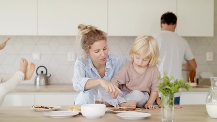 Wall Mural - Young family with two small children indoors in kitchen, making pancakes.