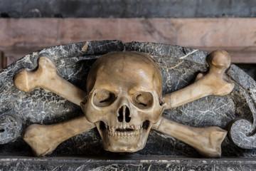 calavera esculpida en piedra de una tumba