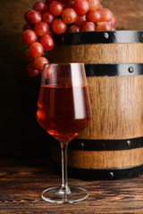 Glass of tasty wine with barrel on wooden table