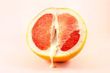 Sexy grapefruit with sperm, erotic concept. Sectional grapefruit is a symbol of the vagina and clitoris. Half grapefruit with dripping white liquid on a pastel background. Erotic concept.