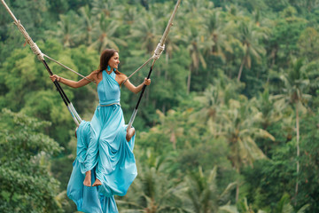 Tanned beautiful woman in a long turquoise dress with a train, riding on a swing. In the background, a rainforest and palm trees. Copy space