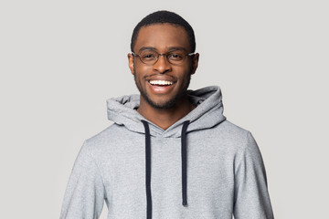 Smiling black male student in stylish hoodie looking at camera.