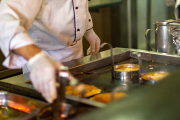 The chef bakes omelettes in the open kitchen of the hotel.