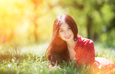 Fototapeten Gelb Young cute woman in red dress relaxing in the park. Beauty nature scene with colorful background, trees at summer season. Outdoor lifestyle. Happy smiling woman lay on green grass