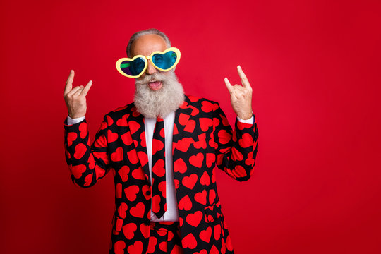 Photo of funky aged man amour cupid character role showing horns fingers excited emotions wear sun specs hearts pattern suit costume shirt tie isolated red color background